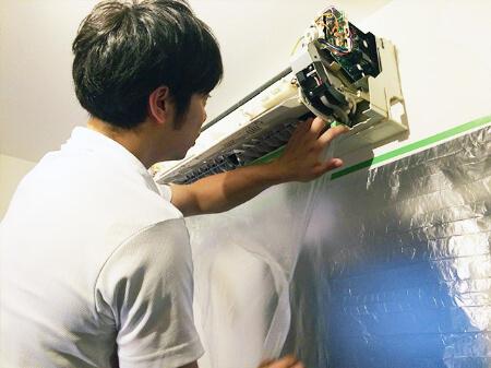 【エアコンクリーニング】電装部分にビニールを巻きつけて養生する